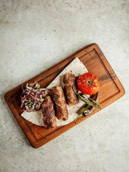 Kebab di lule con pomodoro fritto e cipolle a fette