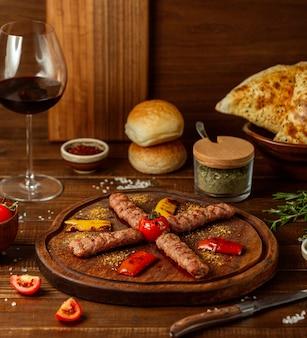 Lule kebab with vegetables on wooden board