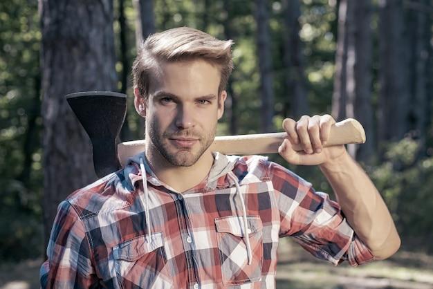 Lumberjack carries axe on shoulder.