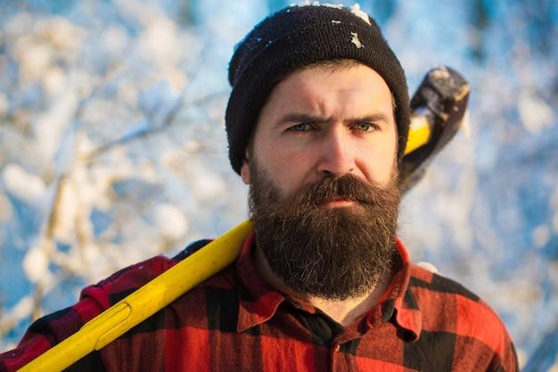 Дровосек в лесу с топором. жестокий бородатый мужчина с бородой и усами в зимний день, заснеженный лес. красивый мужчина, хипстер, лесоруб. привлекательный бородатый мужчина на открытом воздухе зимой.