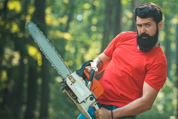 真面目な顔の木こりはチェーンソーを運びます。農林業のテーマ。木こり