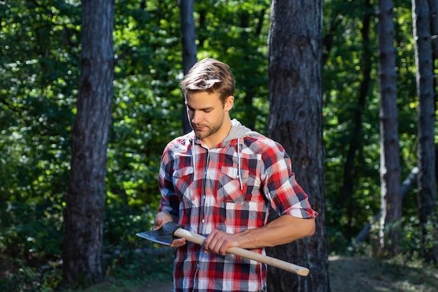 森の背景に斧で立っている木こり。森林破壊は土地の主な原因です