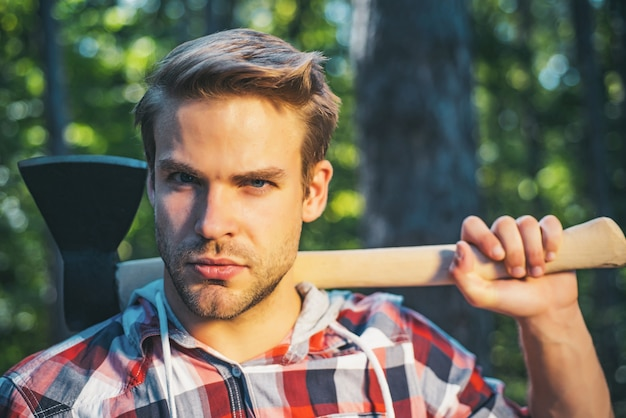 Lumberjack with ax in his hands in a forest
