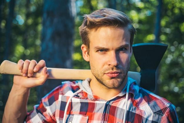 Дровосек с топором в руках. красивый молодой человек с топором возле леса. дрова как возобновляемый источник энергии. человек делает мужскую работу. отдыхает после тяжелой работы.