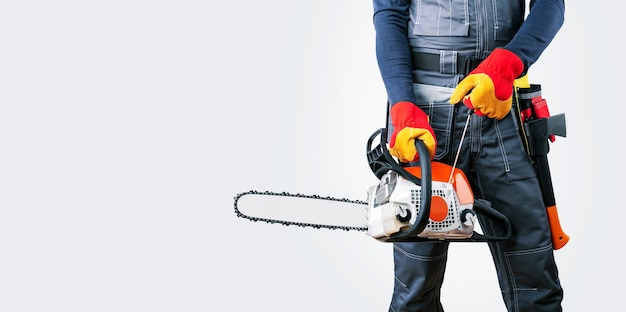 Lumberjack with chainsaw against grey background, banner.