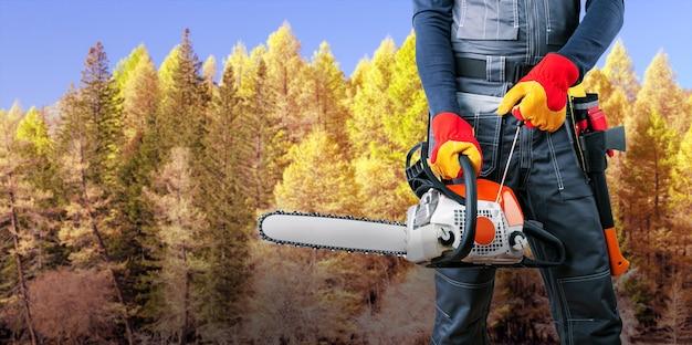 森の中のチェーンソーと斧で木こり。バナー。