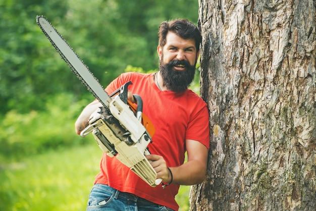 大きな木に寄りかかってチェーンソーを手にした木こり