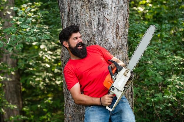 Дровосек с бензопилой на фоне леса человек делает мужскую работу лесоруб с бензопилой в его ...