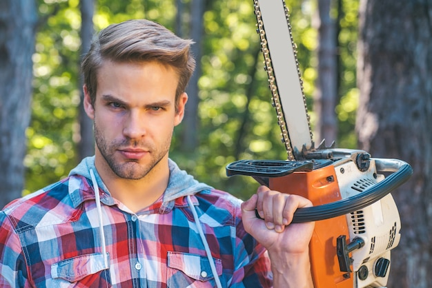 Lumberjack worker standing in the forest with chainsaw. chainsaw.