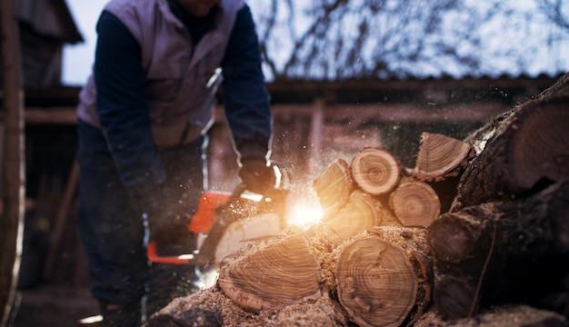 チェーンソー切断木材を持つ木こり労働者。