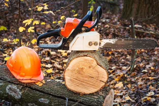 Рабочий инструмент лесоруба бензопила и шлем