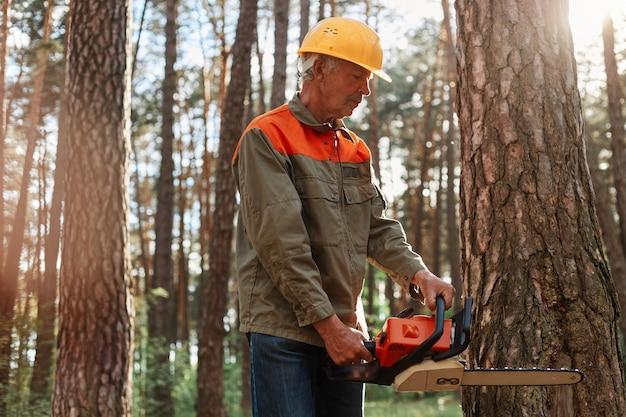 숲에서 전기 톱으로 보호용 작업복과 노란색 헬멧 톱질 나무에 벌목