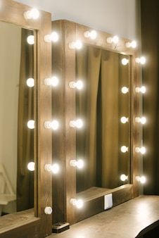 Luminous bulbs are arranged in a row vertically on the surface of the mirror, near the makeup table. illumination of a mirror in a bathroom, copyspace