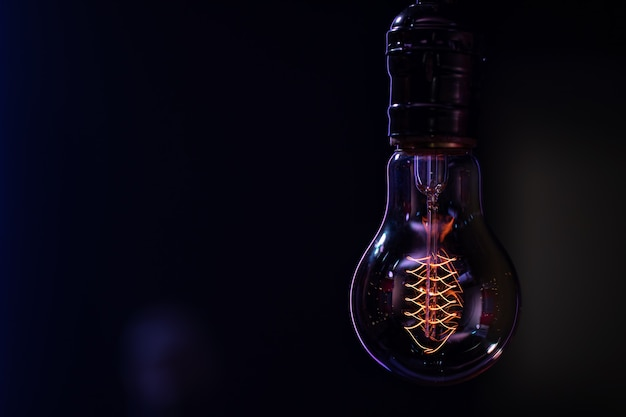 A luminous lamp hangs in the dark blurred background copy space.