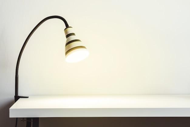 흰색 테이블에 빛나는 줄무늬 램프. 조롱 또는 복사 공간을 위한 흰색 벽입니다.