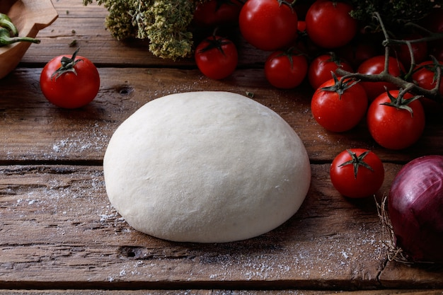 Lump of dough on a wooden table surrounded with tomatoes, pepper and an onion