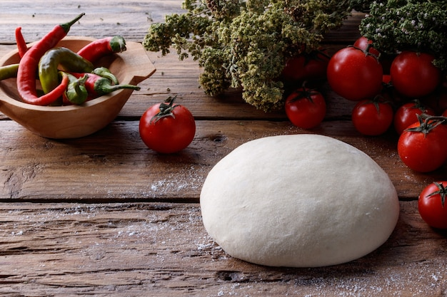 Lump of dough on a wooden table surrounded with tomatoes and pepper