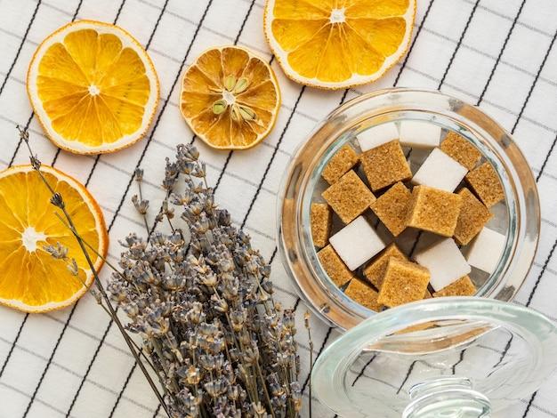 塊のあるインスタントシュガー、ラベンダーの花束、市松模様のテーブルクロスにドライレモンのスライス