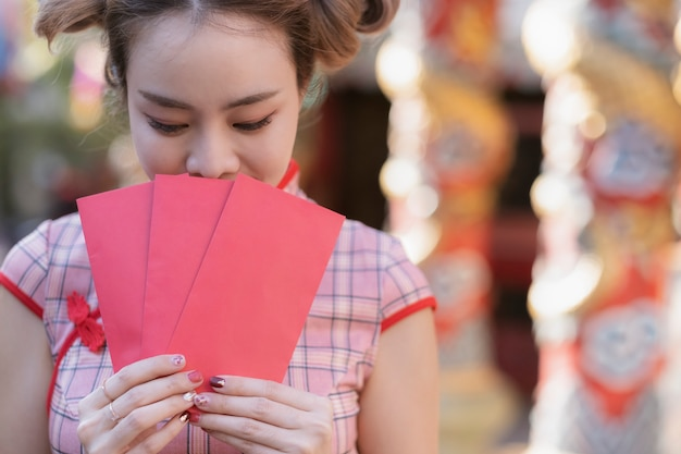 Lunar new year celebrations with red envelopes in hands.