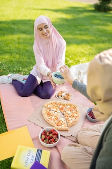 공부 후 점심. 공부 후 피자와 과일을 먹는 히잡의 젊은 여성들