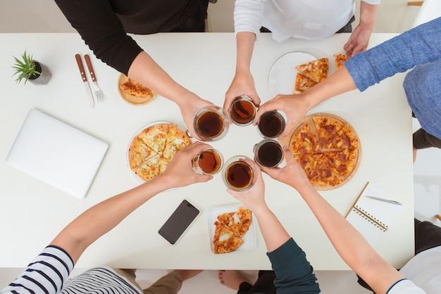 ランチと人のコンセプト。オフィスでピザを食べる幸せなビジネスチーム