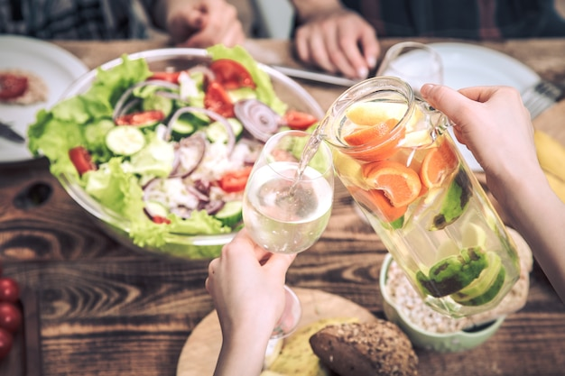 テーブルで昼食、新鮮なフルーツ、飲み物の概念と夏の飲み物を注ぐ