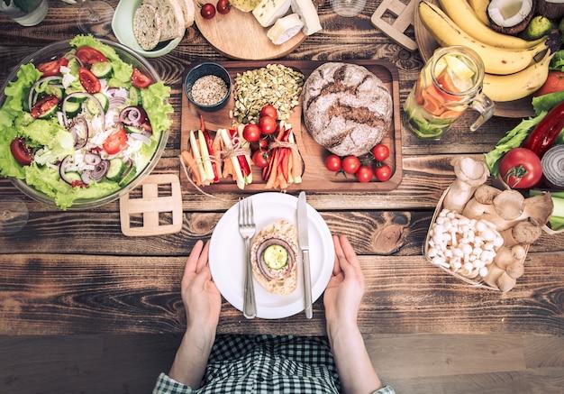 さまざまな食べ物、プレートを持つ女性の手でテーブルで昼食