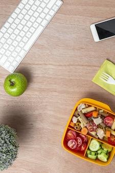 작업 테이블에 점심 도시락에 참치, 체리 토마토, 당근, 오이와 직장 건강 파스타에서 점심 식사. 사무실 개념에 대한 가정 음식