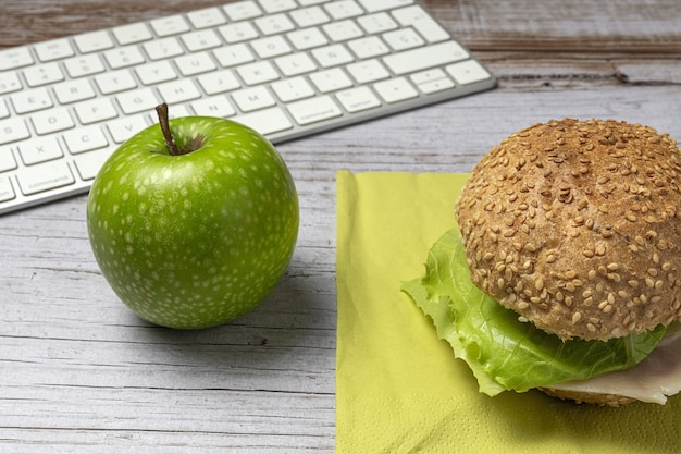 作業台のラップトップの近くの職場の健康的なサンドイッチで昼食。オフィスコンセプトのホームフード