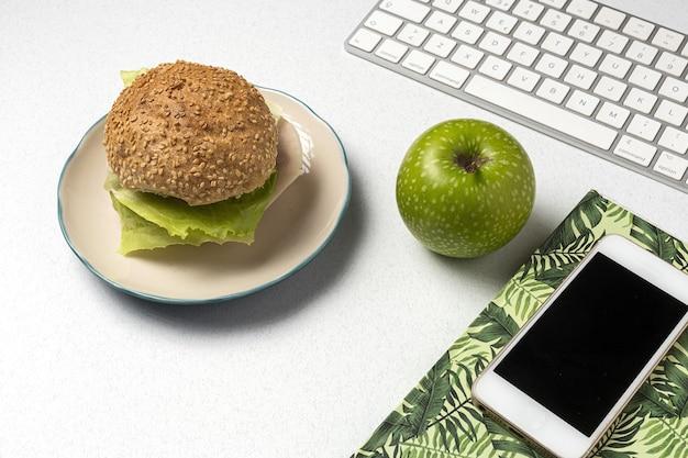 Обед на рабочем месте здоровый бутерброд возле ноутбука на рабочем столе. домашняя еда для концепции офиса