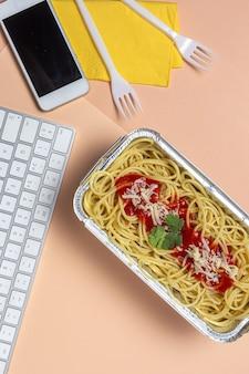 컴퓨터 키보드 작업 테이블에 토마토와 치즈와 함께 직장에서 만든 건강 스파게티에서 점심 식사. 사무실 개념에 대한 가정 음식. 음식을 빼앗아