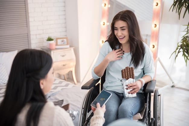 Обеденный перекус. веселая женщина-инвалид и друг едят плитку шоколада и общаются