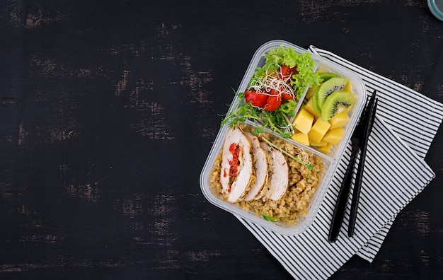 Lunch box  chicken, bulgur, microgreens, tomato  and fruit. healthy fitness food. take away. lunchbox. top view