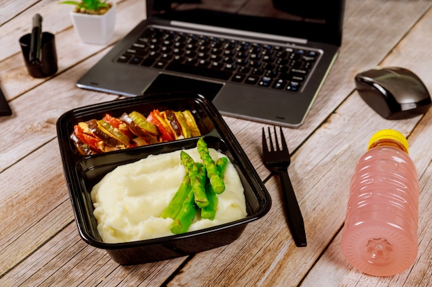 Lunch box container with mashed potato, asparagus and vegetables on wooden table with laptop.