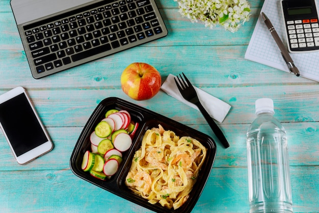 Lunch box container with pasta and shrimps, cucumber and radish on wooden table with laptop.