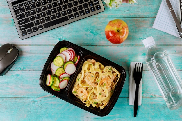 Lunch box container with pasta and shrimps, cucumber and radish.