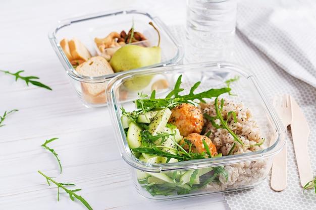 흰색 나무 배경에 오트밀, 오이 샐러드, 견과류, 빵, 배가 채워진 도시락. 도시락 저녁.