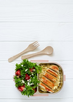 Lunch box full of delicious healthy food: salad, coucous and grilled chicken top view on white wooden table with copy space