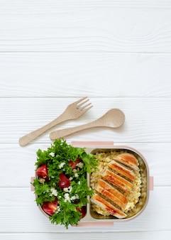 おいしい健康食品がいっぱい入ったお弁当:コピースペース付きの白い木製のテーブルのサラダ、料理、グリルチキントップビュー