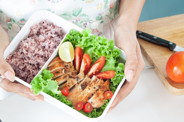 Lunch box, grilled chicken breast with tomatoes, lettuce and steam rice.