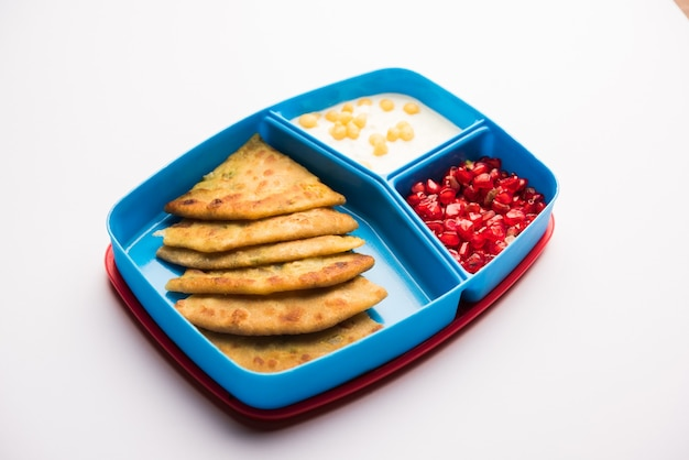 インドの子供向けのランチボックスまたはティフィン、アルパラタ、豆腐ブーンディ、ザクロの種子、セレクティブフォーカスが含まれています