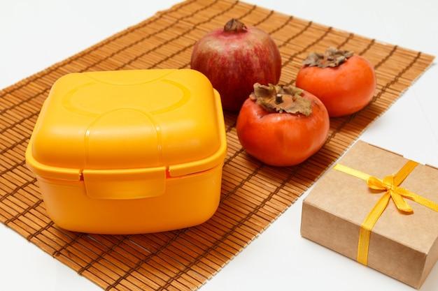 대나무 냅킨에 도시락, 잘 익은 석류, 감 과일