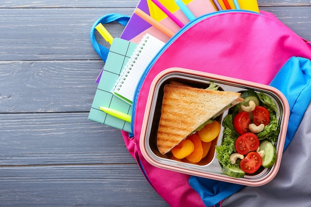 Lunch box and schoolbag on wooden
