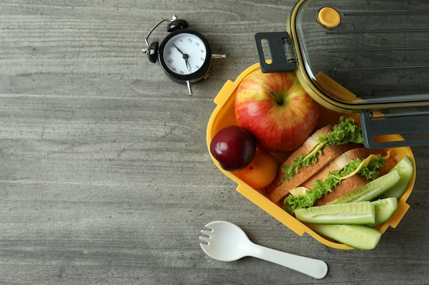 Lunch box and tasty food on gray textured background