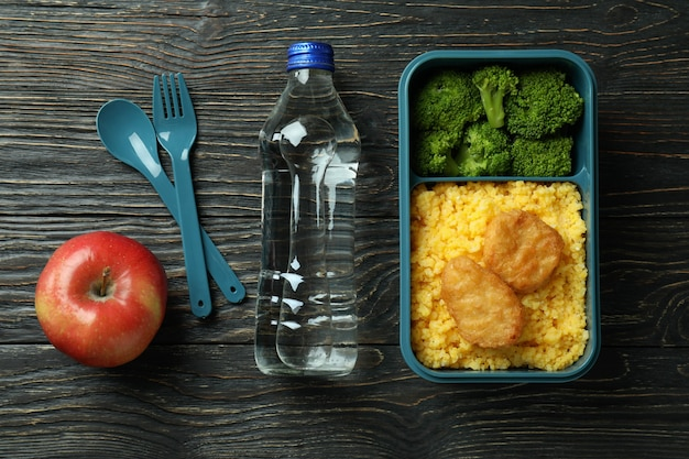 Lunch box and tasty food on wooden background