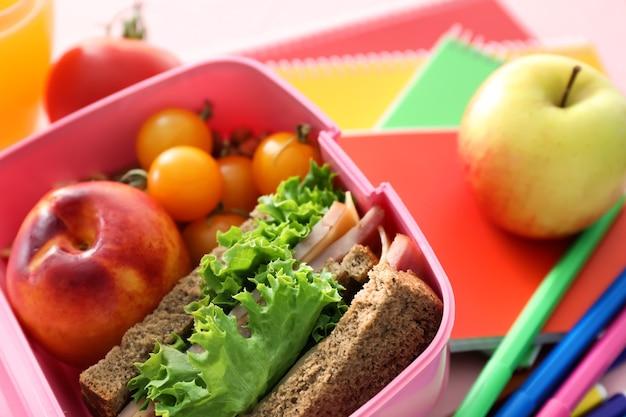 Ланч-бокс с аппетитной едой и канцелярскими принадлежностями на столе, крупным планом