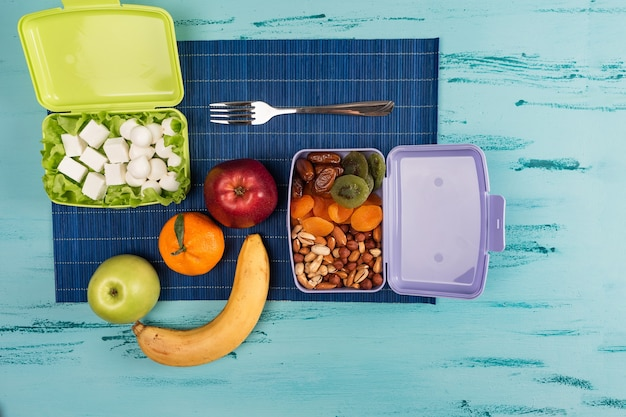 Lunch box with appetizing food and on light wooden table. copy space.