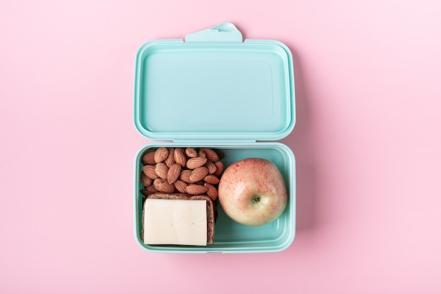 Lunch box with apple, sandwich and almond on pink