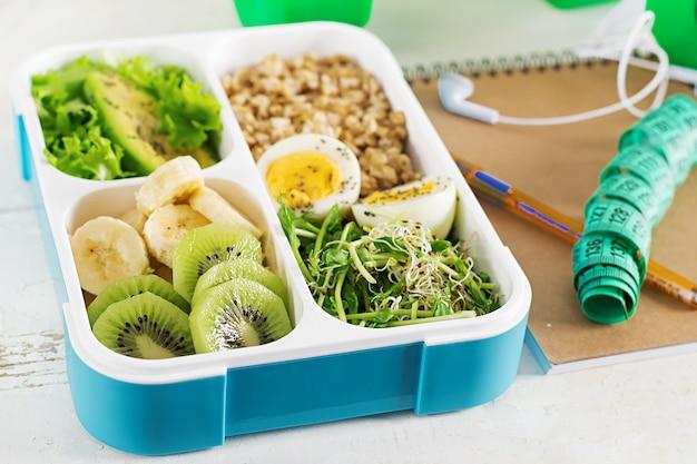 ゆで卵、オートミール、アボカド、マイクログリーン、フルーツの入ったランチボックス。