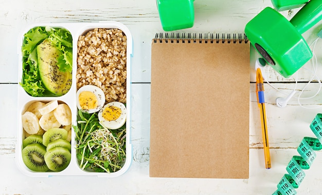 Lunch box  with boiled eggs, oatmeal, avocado, micro greens and fruits.  healthy fitness food. take away. lunchbox. top view